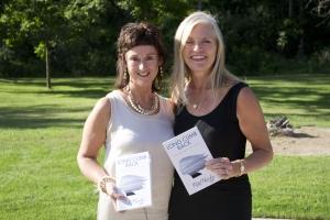Rita Hartley and Sylvie Petroski standing together, each holding a copy of Rita's book Long Climb Back